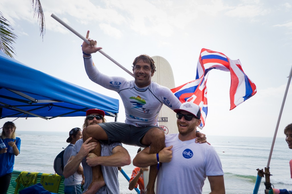 Kai Sallas is chaired up by beach my fellow competitors Ben Skinner (ENG) and Phil Rajzman (BRA), representative of the camaraderie between teams at the ISA World Longboard Surfing Championship. Photo: ISA / Sean Evans
