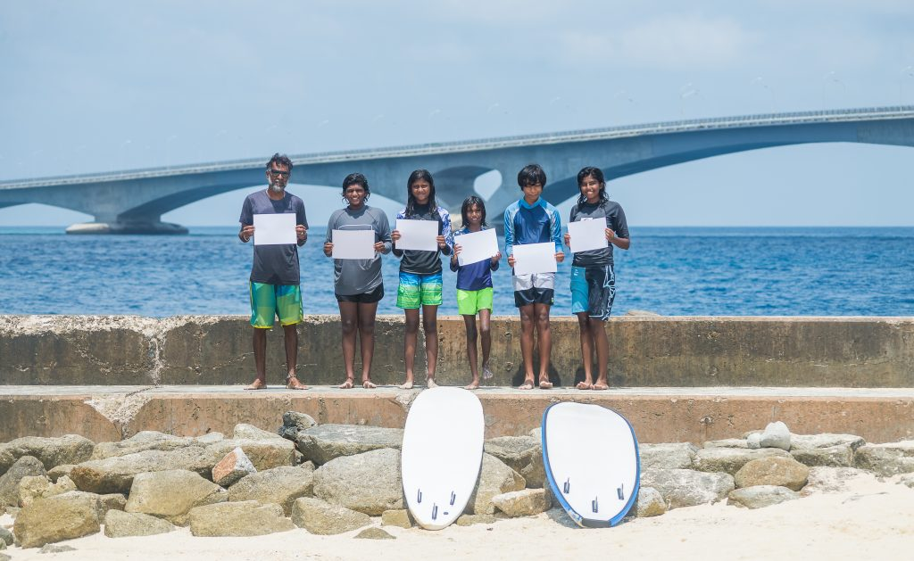 The young girls of @surf_school.mv display white cards in the Maldives.